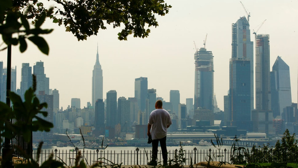 WEEHAWKEN, NJ - AUGUST 17: A man takes a look of the haze over the New York skyline and Empire State Building on August 17, 2018 in Weehawken, New Jersey. Severe thunderstorms and even an isolated tornado could strike New York City on Friday. (Photo by Eduardo Munoz Alvarez/Getty Images