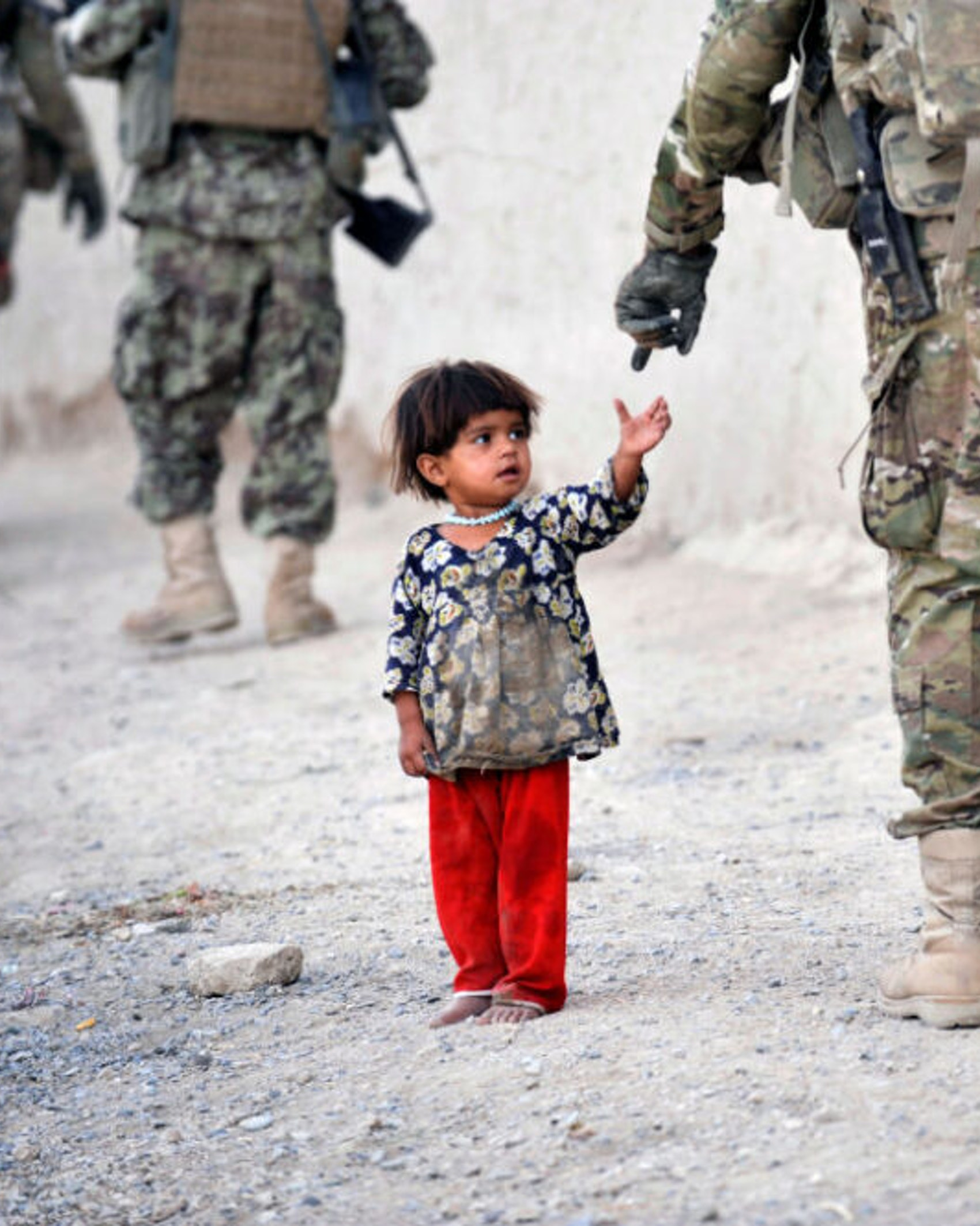 An Afghan girl greets a joint patrol of US troops from the Charlie Company, 2-87 Infantry, 3rd Brigade Combat Team and Afghan National Army soldiers at Kandalay village in the southern Afghan province of Kandahar on August 8, 2011 while US troops launched missile attacks on Taliban targets in nearby Kelawai village killing at least three and capturing two insurgents. US forces push their counterinsurgency efforts to battle for the hearts and minds of the local population.