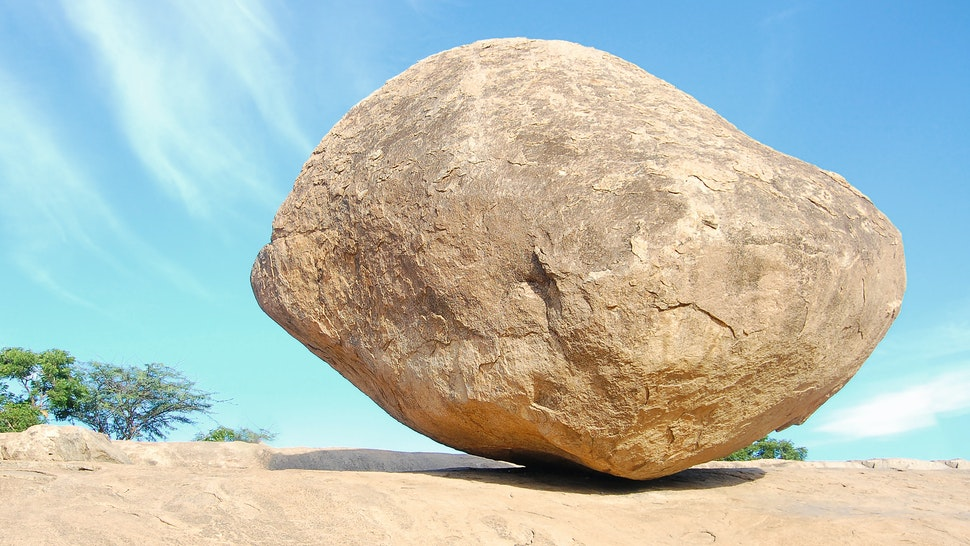 A big huge stone balancing on a slope in Mamallapuram in Tamilnadu. This represents balancing act and can be used to represent humongous task or big task or balance act.