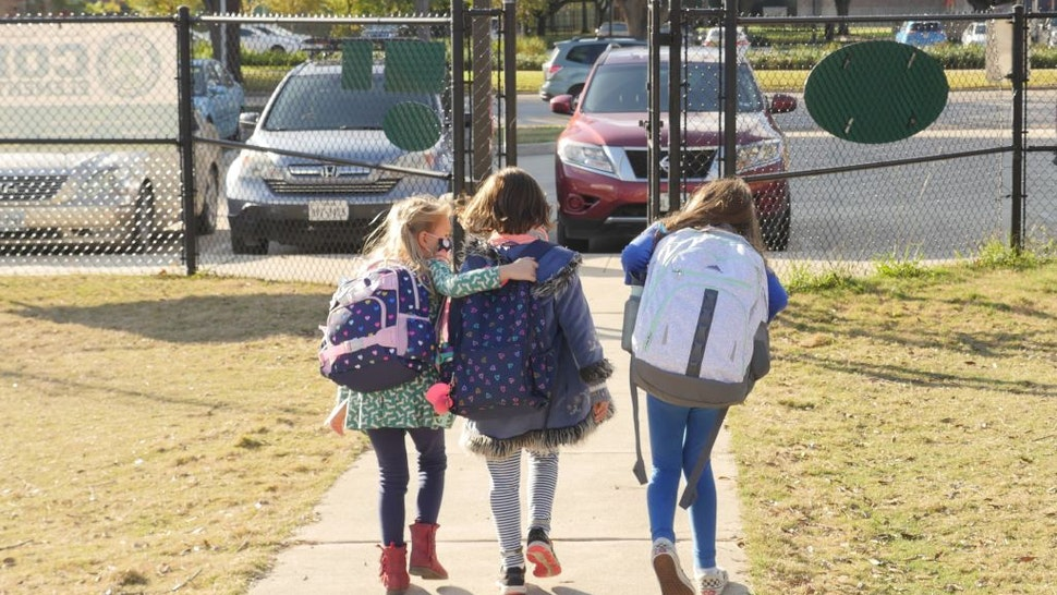 School children wearing facemasks walk outside Condit Elementary School in Bellaire, outside Houston, Texas, on December 16, 2020. - The coronavirus pandemic may be raging in the Houston area, but tens of thousands of students in one district are headed back to in-person classes in January because of poor results while learning from home. The plight of the town of Pasadena is being repeated across America, as educators fret that online learning for children because of the health crisis simply might not work. (Photo by François Picard / AFP) (Photo by FRANCOIS PICARD/AFP via Getty Images)