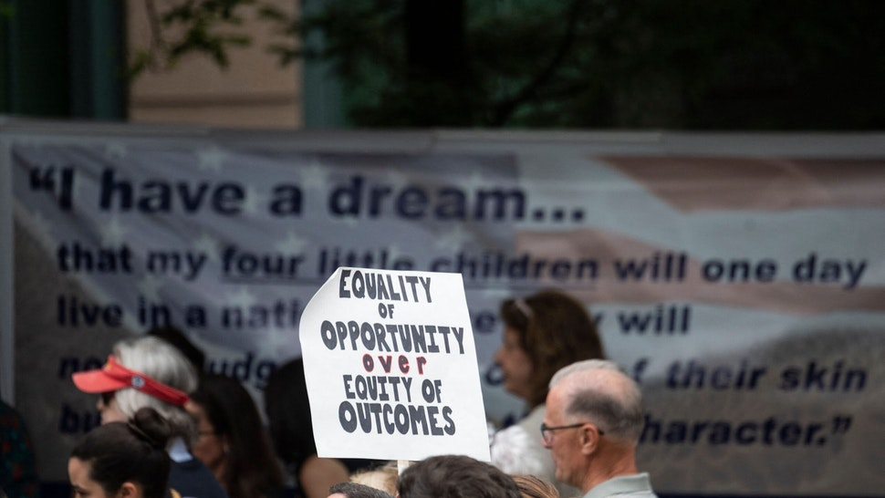 """A participant holds up a sign during a rally against """"critical race theory"""" (CRT) being taught in schools at the Loudoun County Government center in Leesburg, Virginia on June 12, 2021. - """"Are you ready to take back our schools?"""" Republican activist Patti Menders shouted at a rally opposing anti-racism teaching that critics like her say trains white children to see themselves as """"oppressors."""" """"Yes!"""", answered in unison the hundreds of demonstrators gathered this weekend near Washington to fight against """"critical race theory,"""" the latest battleground of America's ongoing culture wars. The term """"critical race theory"""" defines a strand of thought that appeared in American law schools in the late 1970s and which looks at racism as a system, enabled by laws and institutions, rather than at the level of individual prejudices. But critics use it as a catch-all phrase that attacks teachers' efforts to confront dark episodes in American history, including slavery and segregation, as well as to tackle racist stereotypes. (Photo by ANDREW CABALLERO-REYNOLDS / AFP) (Photo by ANDREW CABALLERO-REYNOLDS/AFP via Getty Images)"""