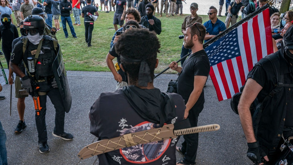 PORTLAND, OR - AUGUST 08: Far-right extremists and anti-fascists argue on August 8, 2021 in Portland, Oregon. The two groups clashed near a religious gathering in downtown Portland for the second day in a row without a police response.