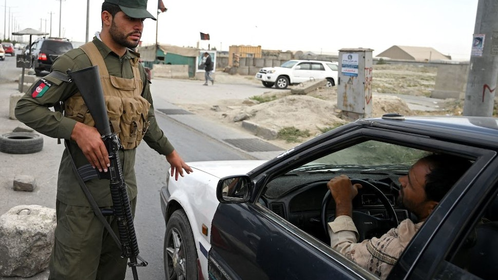 An Afghan policeman speaks to a commuter in car at a checkpoint along the road in Kabul on August 14, 2021. (Photo by WAKIL KOHSAR / AFP) (Photo by WAKIL KOHSAR/AFP via Getty Images)