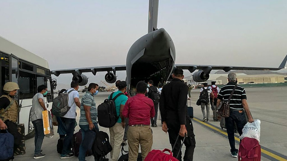 ndian nationals prepare to board an Indian military aircraft at the airport in Kabul on August 17, 2021 to be evacuated after the Taliban stunning takeover of Afghanistan. (Photo by STR / AFP) (Photo by STR/AFP via Getty Images)