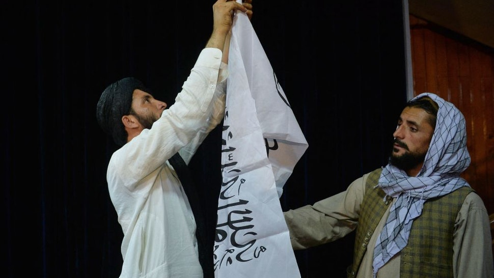Men adjust the Taliban flag before the arrival of Taliban spokesperson Zabihullah Mujahid (unseen) to address the first press conference in Kabul on August 17, 2021 following the Taliban stunning takeover of Afghanistan. (Photo by Hoshang Hashimi / AFP) (Photo by HOSHANG HASHIMI/AFP via Getty Images)