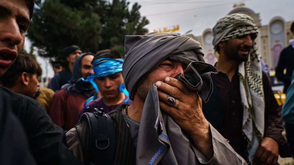 KABUL, AFGHANISTAN -- AUGUST 17, 2021: A man cries as he watches fellow Afghans get wounded after Taliban fighters use guns fire, whips, sticks and sharp objects to maintain crowd control over thousands of Afghans who continue to wait outside the Kabul Airport for a way out, on airport road in Kabul, Afghanistan, Tuesday, Aug. 17, 2021. At least half dozen were wounded, within the hour of violent escalation, including a woman and her child. (MARCUS YAM / LOS ANGELES TIMES)