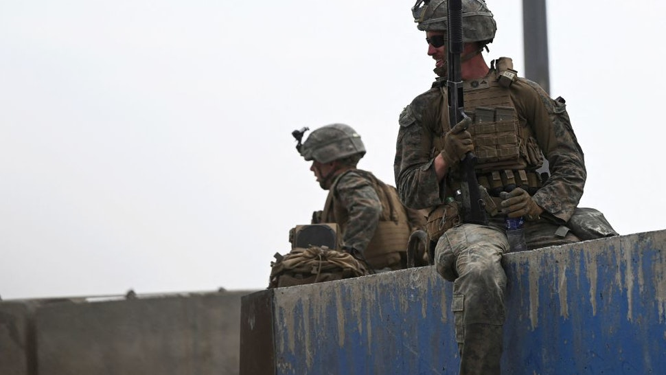 US soldiers sit on a wall as Afghans gather on a roadside near the military part of the airport in Kabul on August 20, 2021, hoping to flee from the country after the Taliban's military takeover of Afghanistan. (Photo by Wakil KOHSAR / AFP) (Photo by WAKIL KOHSAR/AFP via Getty Images)