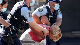 Police officers detain a protestor in Sydney on August 21, 2021, following calls for an anti-lockdown protest rally amid a fast-spreading coronavirus outbreak.