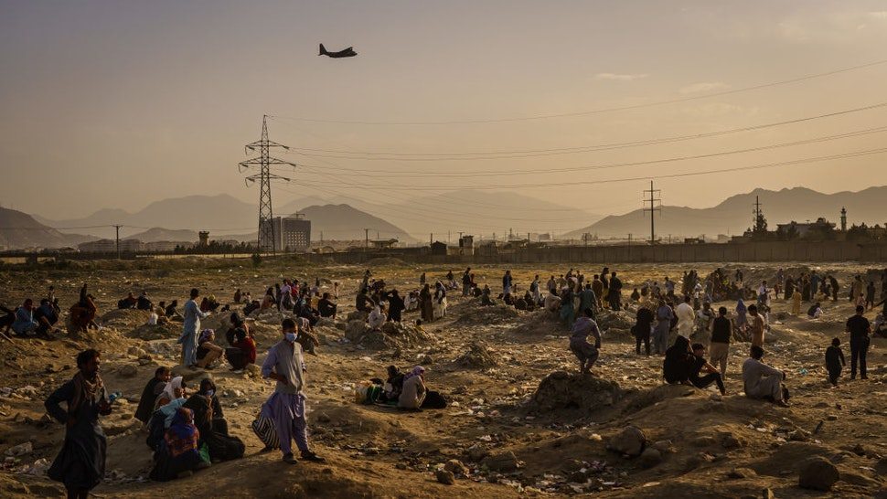 KABUL, AFGHANISTAN -- AUGUST 23, 2021: A military transport plane launches off while Afghans who cannot get into the airport to evacuate, watch and wonder while stranded outside, in Kabul, Afghanistan, Monday, Aug. 23, 2021.
