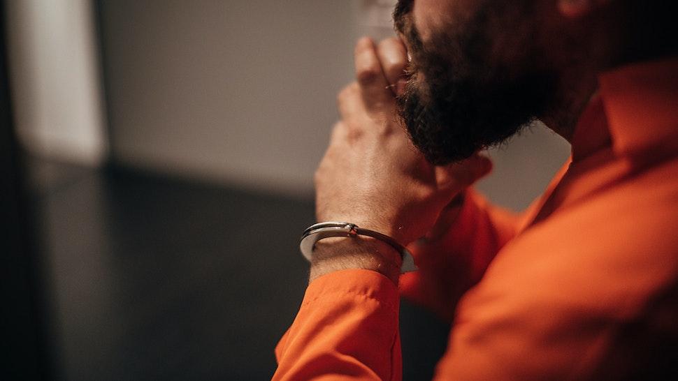 Prisoner in orange jumpsuit sitting in prison visiting room - stock photo