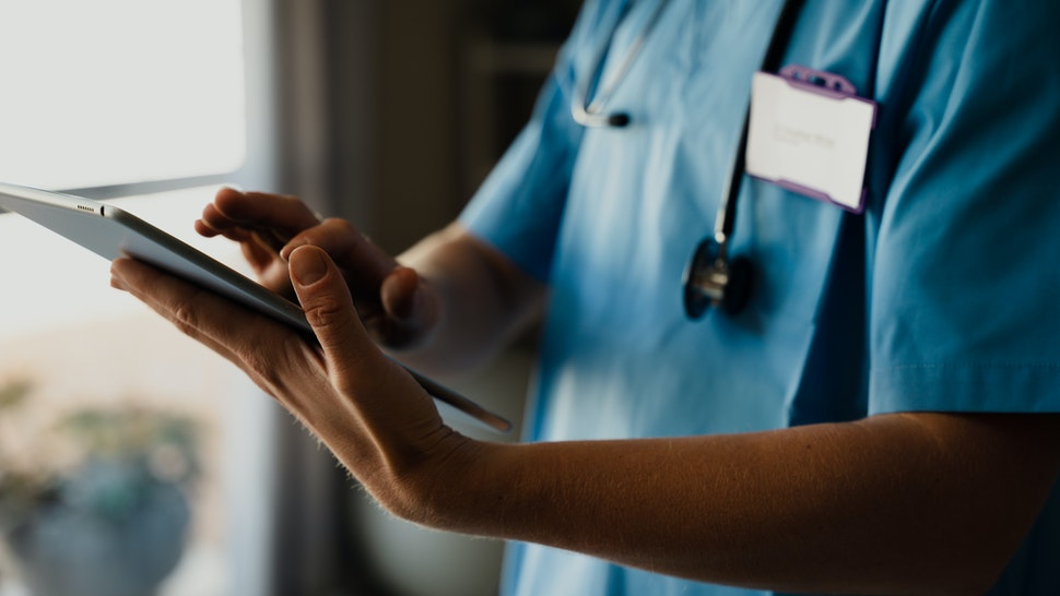 Close-up of female doctor in scrubs with digital tablet, typing and completing checklist - stock photo