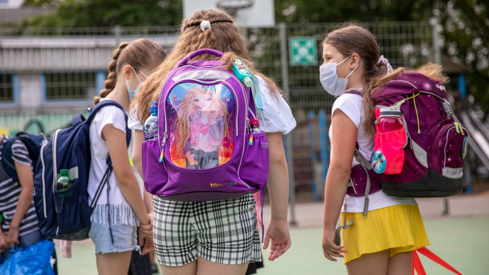 BERLIN, GERMANY - AUGUST 10: Children wearing protective face masks arrive for the first day of classes of the new school year at the GuthsMuths elementary school during the coronavirus pandemic on August 10, 2020 in Berlin, Germany. Classes at schools across Germany are beginning this month with face mask requirements varying by state. Coronavirus infection rates are climbing again in Germany, from an average of 400 new cases per day about two weeks ago to over 1,100 yesterday, according to the Robert Koch Institute. (Photo by Maja Hitij/Getty Images)