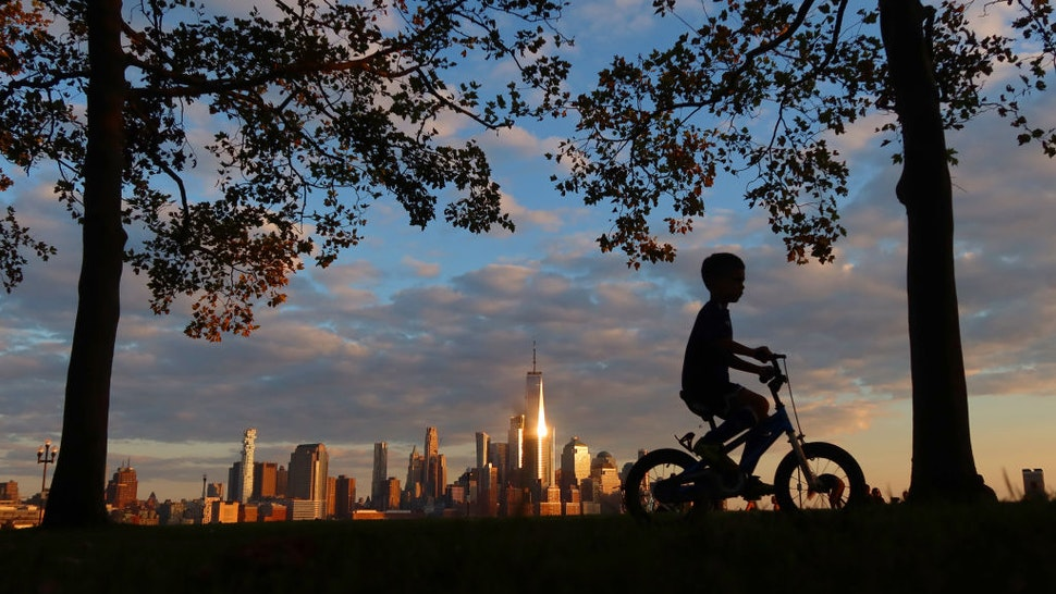 HOBOKEN, NJ - OCTOBER 5: A child rides his bicycle through the park on Pier A as the sun sets on lower Manhattan and One World Trade Center in New York City on October 5, 2020 in Hoboken, New Jersey. (