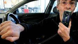 A man holds an electronic ethylotest device that prevents the start of the vehicle in case of positive control, in Reims, northeastern France, on December 1, 2016. This device is tested in several French departments from December 1 and will be mandatory for people in case of a positive test. The lettering on the display reads 'Test ok'. / AFP / François NASCIMBENI