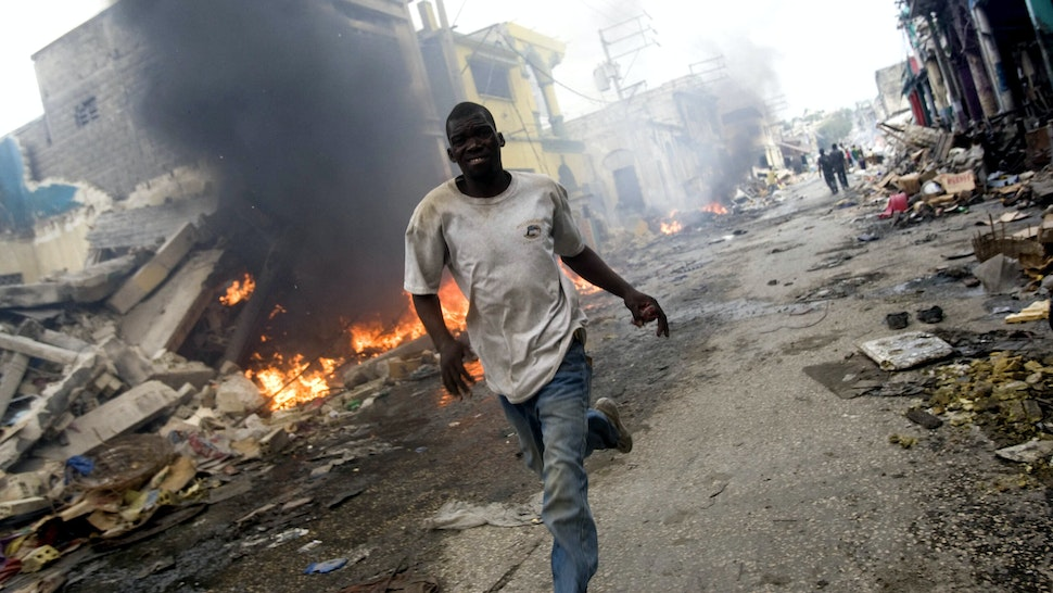 PORT-AU-PRINCE, HAITI - JANUARY 25: In this handout image provided by the United Nations Stabilization Mission in Haiti (MINUSTAH), A man runs besides a fire in downtown on January 25, 2010 in Port-au-Prince, Haiti. Haiti is trying to recover from a powerful 7.0-strong earthquake that struck on January 12 and devastated the country, displacing millions and killing tens of thousands.