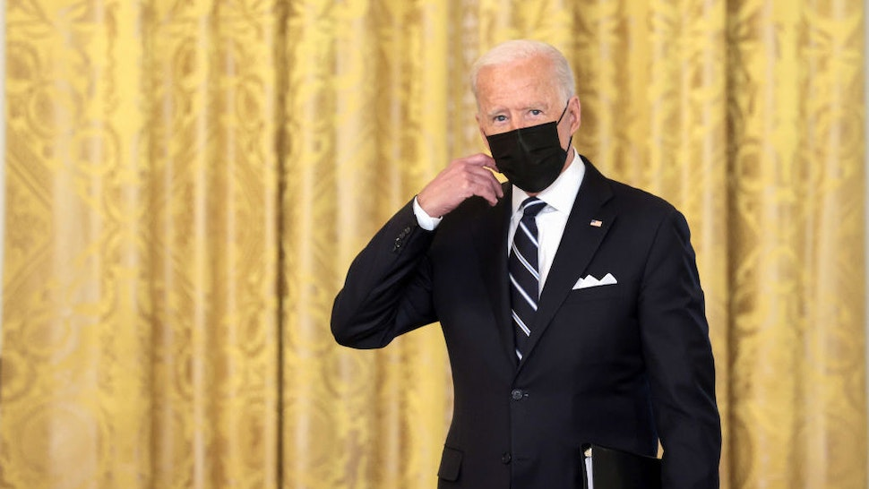 WASHINGTON, DC - AUGUST 18: U.S. President Joe Biden removes his face mask as he arrives to deliver remarks on the COVID-19 response and the vaccination program in the East Room of the White House on August 18, 2021 in Washington, DC. During his remarks, President Biden announced that he is ordering the United States Department of Health and Human Services to require nursing homes to have vaccinated staff in order for them to receive Medicare and Medicaid funding. The President also announced that Americans would be able to receive a third booster shot against Covid-19. (Photo by Anna Moneymaker/Getty Images)