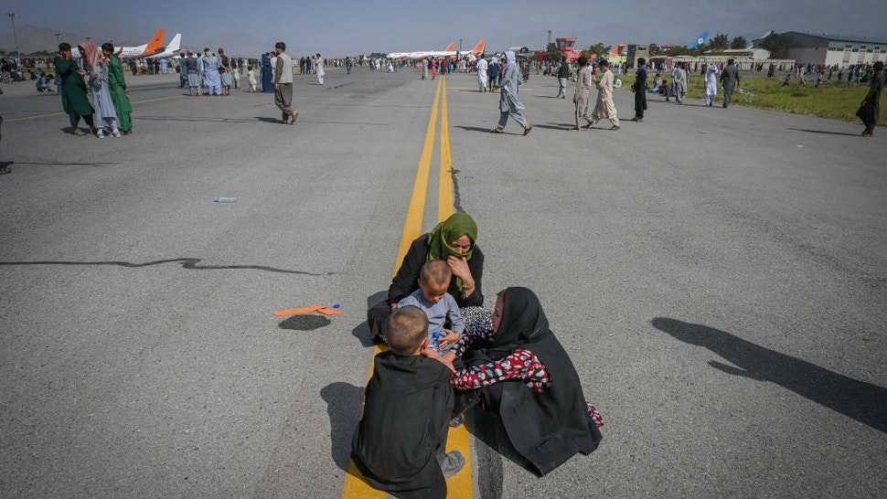 Afghan people sit along the tarmac as they wait to leave the Kabul airport in Kabul on August 16, 2021, after a stunningly swift end to Afghanistan's 20-year war, as thousands of people mobbed the city's airport trying to flee the group's feared hardline brand of Islamist rule.