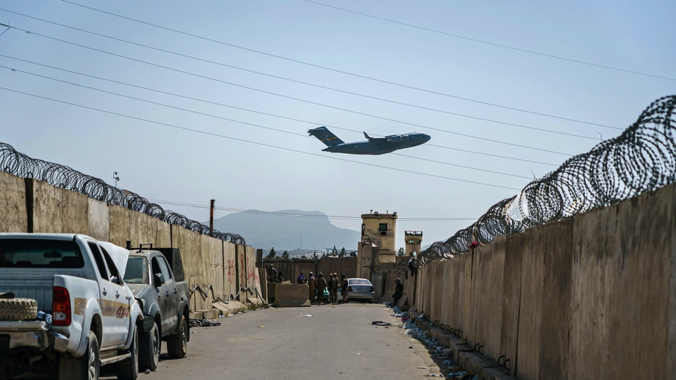 KABUL, AFGHANISTAN -- AUGUST 29, 2021: A C-17 Globemaster takes off as Taliban fighters secure the outer perimeter, alongside the American controlled side of of the Hamid Karzai International Airport in Kabul, Afghanistan, Sunday, Aug. 29, 2021.