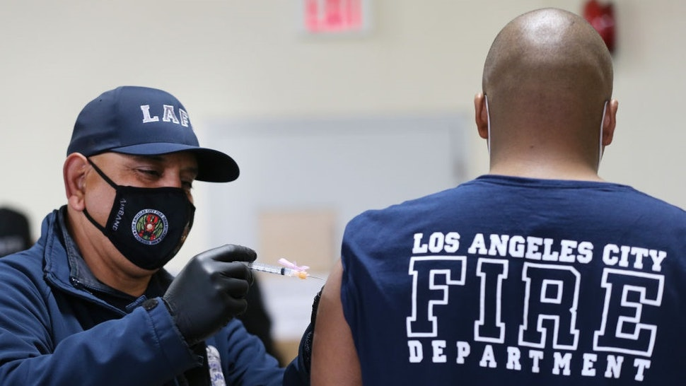 LOS ANGELES, CALIFORNIA - JANUARY 29: A Los Angeles Fire Department (LAFD) firefighter receives a Moderna COVID-19 vaccination dose from firefighter Michael Perez (L) at a fire station on January 29, 2021 in Los Angeles, California.
