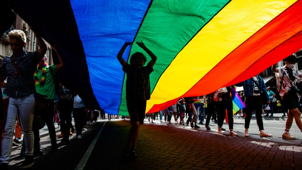 A boy is dancing under the big rainbow flag, during the celebration of the Pride walk in Amsterdam, on August 7th, 2021.