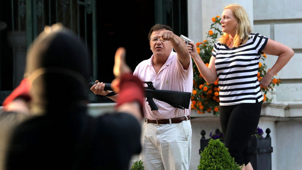 Armed homeowners Mark T. and Patricia N. McCloskey stand in front their house as they confront protesters marching to St. Louis Mayor Lyda Krewson's house on June 28, 2020. (Laurie Skrivan/St. Louis Post-Dispatch/TNS)