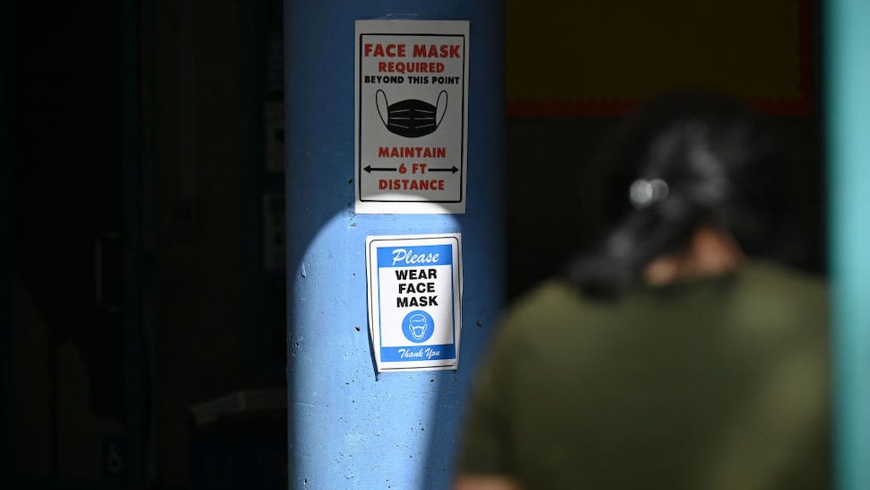 A sign at the entrance to a charter school advises that masks are required to enter, in Los Angeles, California, August 11, 2021. - All teachers in California will have to be vaccinated against Covid-19 or submit to weekly virus tests, Governor Gavin Newsom announced on August 11, as authorities grapple with exploding infection rates. The number of people testing positive for the disease has surged in recent weeks, with the highly infectious Delta variant blamed for the bulk of new cases.