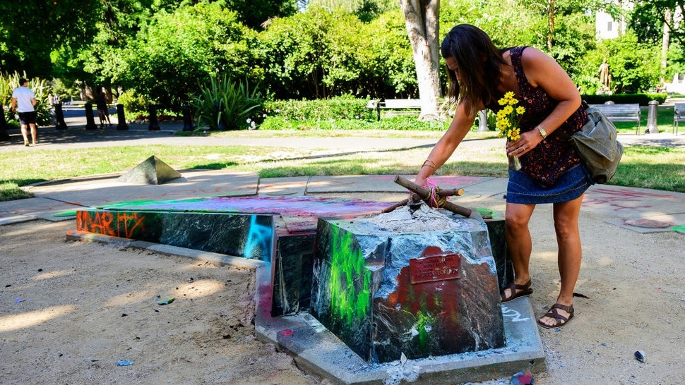 Devout Catholic Audrey Ortega creates a memorial at the former site of a statue memorializing Father Junipero Serra, a Spanish priest and friar who founded missions along California's coast in the 1700s, in Capitol Park on Sunday, July 5, 2020.