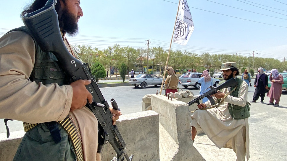 TOPSHOT - Taliban fighters stand guard at an entrance gate outside the Interior Ministry in Kabul on August 17, 2021.