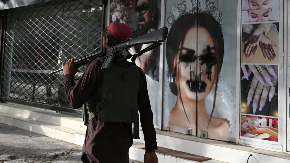 A Taliban fighter walks past a beauty saloon with images of women defaced using a spray paint in Shar-e-Naw in Kabul on August 18, 2021.