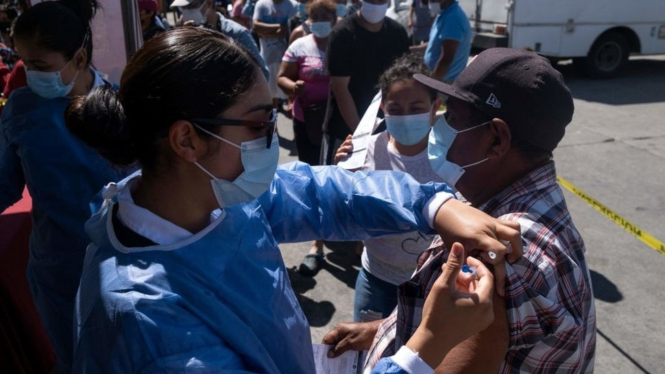 An asylum seeker camping at El Chaparral crossing port is vaccinated against COVID-19 in Tijuana, Baja California state, Mexico, on the border with the US, on August 3, 2021.