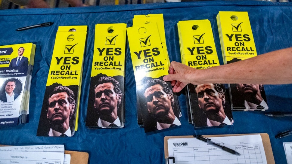 IRVINE, CA - JULY 31: A woman reaches for recall door hangers at a pro-recall rally at an Irvine hotel on Saturday, July 31, 2021, for the upcoming California Gubernatorial Recall Election against Governor Gavin Newsom to be held on September 14, 2021.