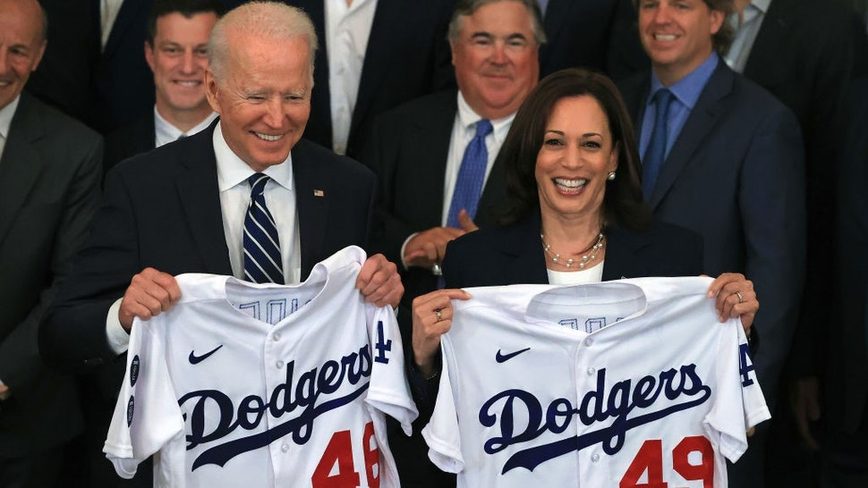 WASHINGTON, DC - JULY 02: U.S. President Joe Biden and Vice President Kamala Harris pose with the jerseys given to them by the 2020 World Series champion Los Angeles Dodgers during a congratulatory event in the East Room of the White House on July 02, 2021 in Washington, DC. The Dodgers defeated the Tampa Bay Rays to win the championship series at the end of an abbreviated season due to the coronavirus. (Photo by