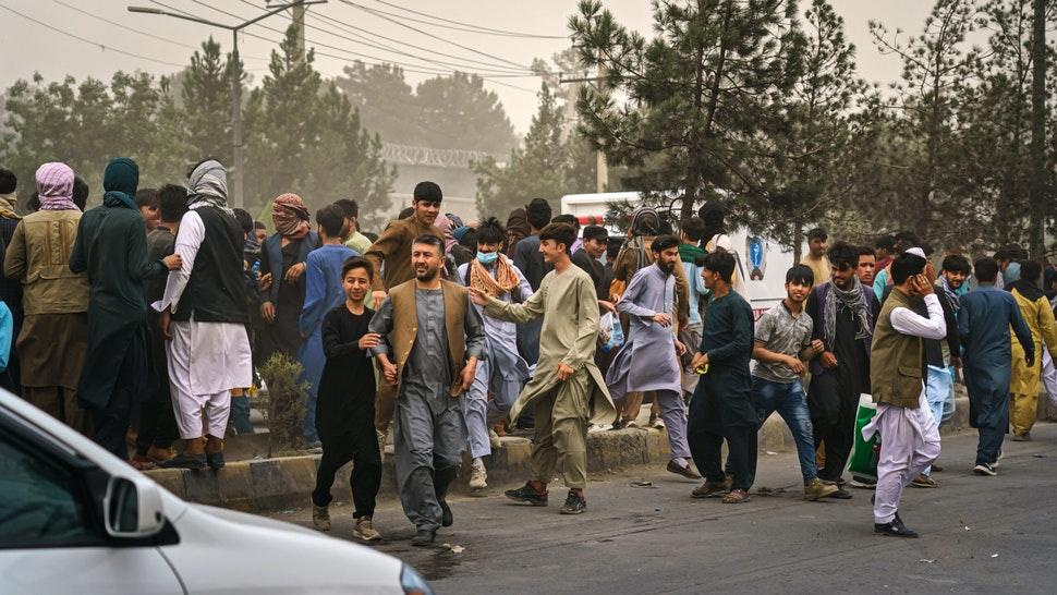 KABUL, AFGHANISTAN -- AUGUST 17, 2021: Afghans run away after Taliban fighters use guns fire, whips, sticks and sharp objects to maintain crowd control over thousands of Afghans who continue to wait outside the Kabul Airport for a way out, on airport road in Kabul, Afghanistan, Tuesday, Aug. 17, 2021. At least half dozen were wounded, within the hour of violent escalation, including a woman and her child.