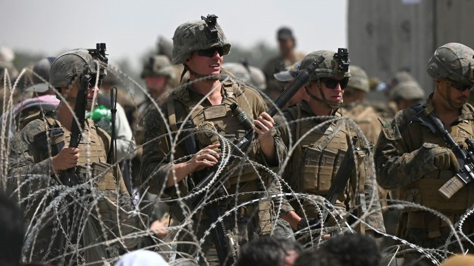 TOPSHOT - US soldiers stand guard behind barbed wire as Afghans sit on a roadside near the military part of the airport in Kabul on August 20, 2021, hoping to flee from the country after the Taliban's military takeover of Afghanistan. (Photo by Wakil KOHSAR / AFP) (Photo by