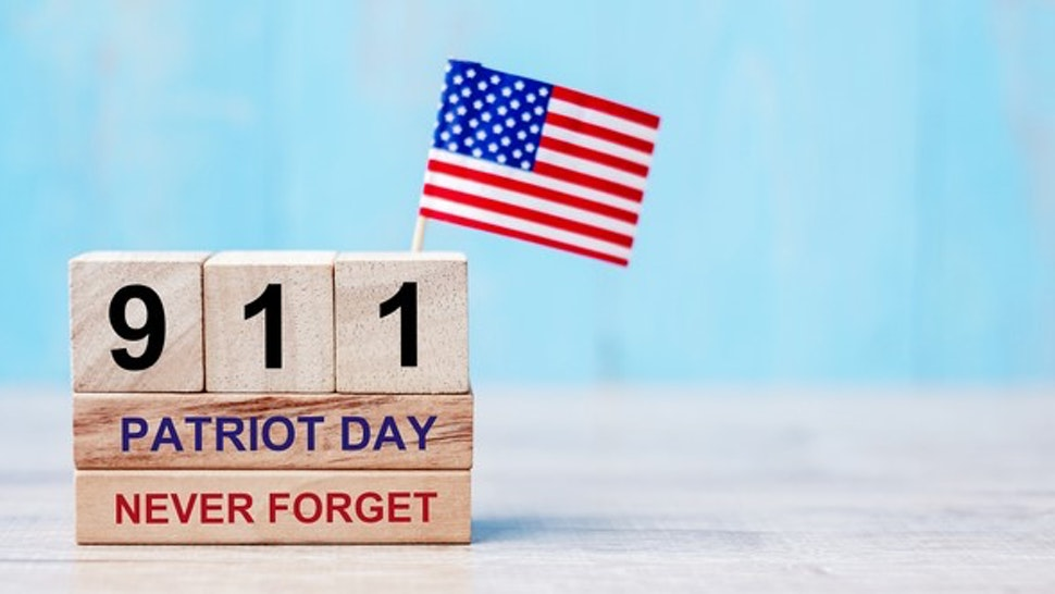 Close-Up Of Patriot Day Text With Number And American Flag On Table