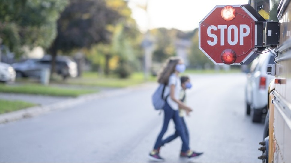 School bus stop sign for children to pass - stock photo A STOP sign is out by the school bus and children can be seeing crossing the road in front of the school bus. FatCamera via Getty Images