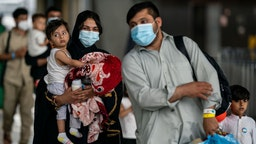 DULLES, VA - AUGUST 31: Evacuees who fled Afghanistan walk through the terminal to board buses that will take them to a processing center, at Dulles International Airport on Tuesday, Aug. 31, 2021. Refugees continue to arrive in the United States, after the US withdrew troops from Afghanistan.