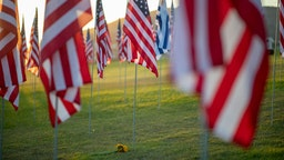 MALIBU, CA - SEPTEMBER 10: Sunflowers are laid on the ground during the 14th annual Waves of Flags on the eve of the 20th anniversary of the September 11 terror attacks in Alumni Park at Pepperdine University on September 10, 2021 in Malibu, California. The 14th annual Waves of Flags display consists of a flag for each life lost and includes a national flag for each foreign nation that lost a citizen during the 9/11 attacks. The nation is marking the 20th anniversary of the terror attacks of September 11, 2001, when the terrorist group al-Qaeda flew hijacked airplanes into the World Trade Center, Shanksville, PA and the Pentagon, killing nearly 3,000 people.