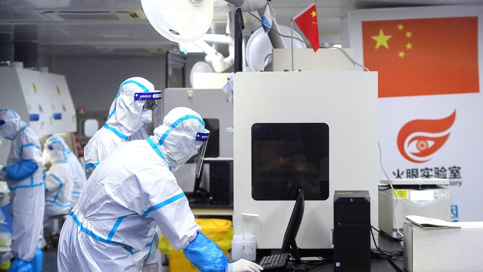This photo taken on August 4, 2021 shows laboratory technicians wearing personal protective equipment (PPE) working on samples to be tested for the Covid-19 coronavirus at the Fire Eye laboratory, a Covid-19 testing facility, in Wuhan in China's central Hubei province. - China OUT