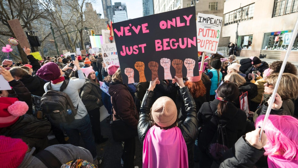 """A demonstrator holds up a banner saying """"We've Only Just Begun"""" during the second annual Women's March in the borough of Manhattan in New York City, U.S. on Saturday, January 20, 2018."""