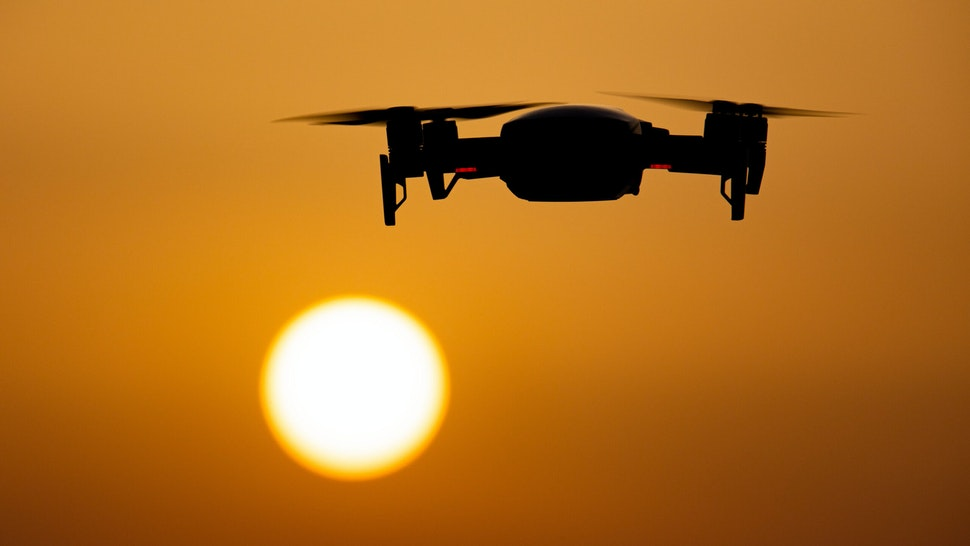A quadcopter drone hovering during a flight in front of the sun. The flying drone is seen as a dark silhouette against the spectacular colorful sunset sky and the sun while the UAV is able to capture aerial videography and photography via a remote control. The specific drone is a DJI Mavic Air. The Unmanned aerial vehicle is popular for recreational usage by tourists as the technology is accessible to everybody in low cost but also has many professional applications Sani Beach area, Halkidiki, Greece on July 15, 2021
