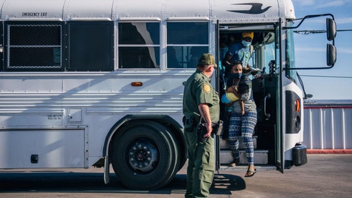 DEL RIO, TEXAS - SEPTEMBER 22: Migrants exit a Border Patrol bus and prepare to be received by the Val Verde Humanitarian Coalition after crossing the Rio Grande on September 22, 2021 in Del Rio, Texas. Thousands of immigrants, mostly from Haiti, seeking asylum have crossed the Rio Grande into the United States. Families are living in makeshift tents under the international bridge while waiting to be processed into the system. U.S. immigration authorities have been deporting planeloads of migrants directly to Haiti while others have crossed the Rio Grande back into Mexico.
