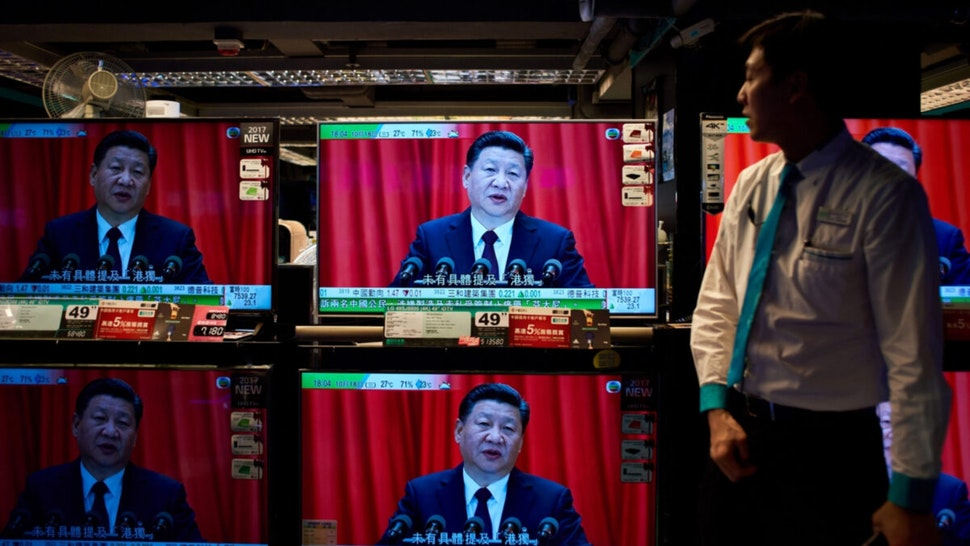 An electronics shop employee in Hong Kong on October 18, 2017 looks at television sets showing a news report on China's President Xi Jinping's speech at the opening session of the Chinese Communist Party's five-yearly Congress at the Great Hall of the People in Beijing.