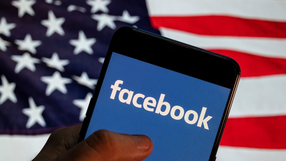 CHINA - 2021/04/02: In this photo illustration the American online social media and social networking service company Facebook (FB) logo is seen on an Android mobile device with United States of America (USA), commonly known as the United States (U.S. or US), flag in the background.