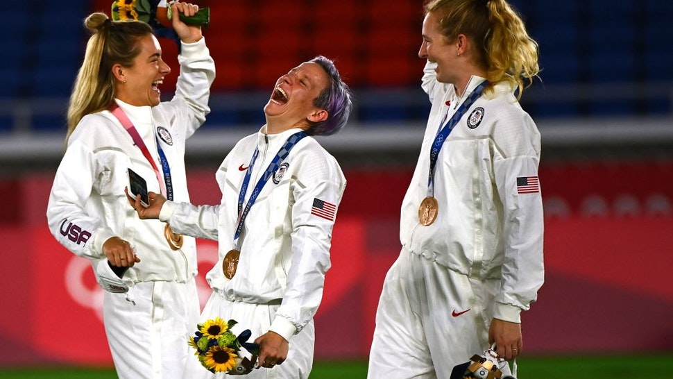 TOPSHOT - Bronze medallist USA's forward Megan Rapinoe (C) smiles during the victory ceremony after the Tokyo 2020 Olympic Games women's final football match at the International Stadium Yokohama in Yokohama on August 6, 2021. (Photo by Loic VENANCE / AFP) (Photo by LOIC VENANCE/AFP via Getty Images)