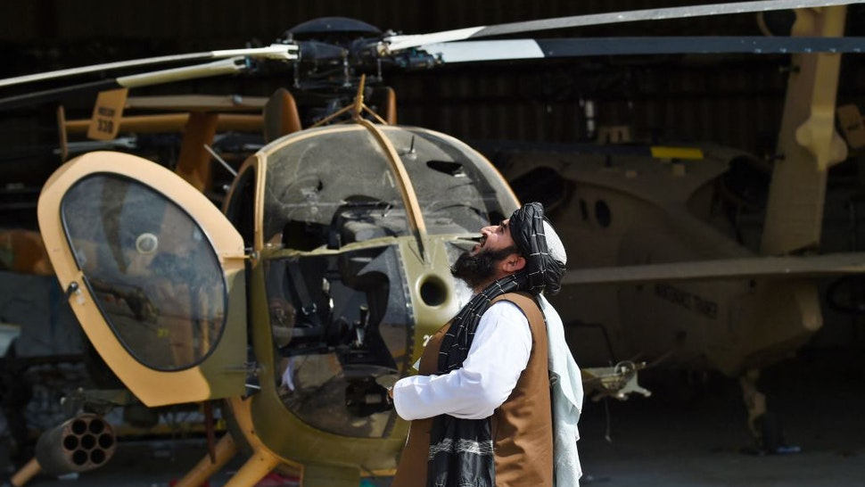 Taliban member looks up standing next to a damaged helicopter at the airport in Kabul on August 31, 2021, after the US has pulled all its troops out of the country to end a brutal 20-year war -- one that started and ended with the hardline Islamist in power. (Photo by Wakil KOHSAR / AFP) (Photo by WAKIL KOHSAR/AFP via Getty Images)