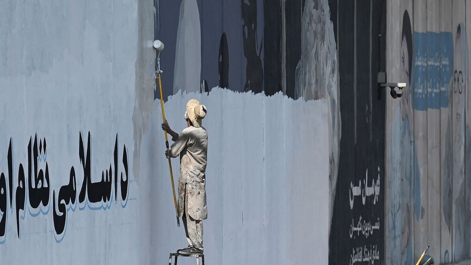 TOPSHOT - A man paints over murals on a concrete wall along a street in Kabul on September 4, 2021. - Within weeks of the Taliban taking the capital, many of the street art pieces have been painted over, replaced by drab propaganda slogans as the Islamist reimpose their austere vision on Afghanistan. (Photo by Aamir QURESHI / AFP) (Photo by AAMIR QURESHI/AFP via Getty Images)