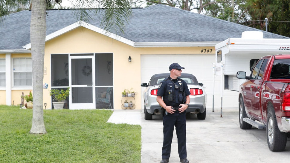 A North Port Police officer stands in the driveway of the family home of Brian Laundrie, who is a person of interest after his fiancé Gabby Petito went missing on September 20, 2021 in North Port, Florida.