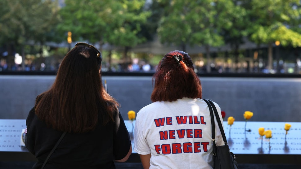 People attend the annual 9/11 Commemoration Ceremony at the National 9/11 Memorial and Museum on September 11, 2021 in New York City. During the ceremony, six moments of silence were held, marking when each of the World Trade Center towers was struck and fell and the times corresponding to the attack on the Pentagon and the crash of Flight 93.