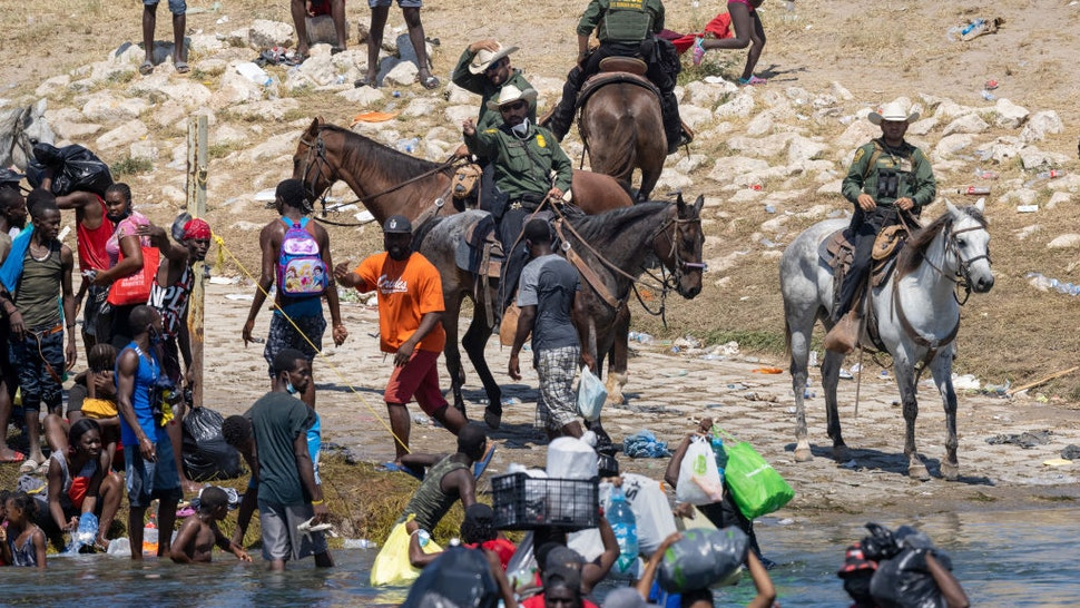 U.S. Border Patrol agents interact with Haitian immigrants on the bank of the Rio Grande in Del Rio, Texas on September 20, 2021 as seen from Ciudad Acuna, Mexico.